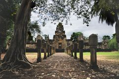 Laterite stone paved walkway with free-standing stone posts to the courtyard gates of ancient Khmer temple built of red sandstone stock photo