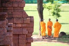 Lateritestenen av grunden av den huvudsakliga stupaen på Khao Klang Nok och fokuserar ut tre thailändska munkar som står under tr fotografering för bildbyråer