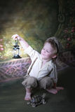Latern Boy. Boy holding up lantern, turtle at feet royalty free stock photography