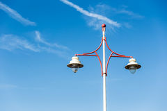 Latern post light on a blue sky with just a few clouds Royalty Free Stock Image