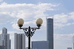 Laterne auf dem Hintergrund von Wolkenkratzern und von Himmel Stockfotografie