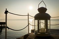 Laterne auf dem Meer bei Sonnenuntergang Stockbild