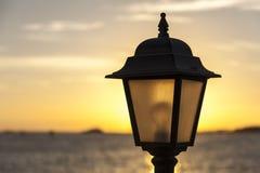 Laterne gegen den Hintergrund des Sonnenuntergangs und des Meeres stockfotos
