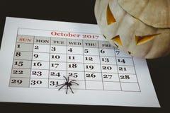 Laterne Jacks O mit künstlicher Spinne auf Kalender über schwarzem Hintergrund Lizenzfreie Stockfotos