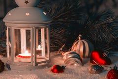Laterne mit einer brennenden Kerze und Weihnachtsdekorationen auf einer schneebedeckten Tabelle lizenzfreies stockfoto