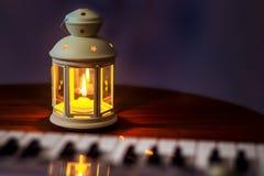 Laterne mit einer Kerze nahe dem Klavier Abendkonzert Ausführung von Musik in einem romantischen setting_ lizenzfreie stockfotografie