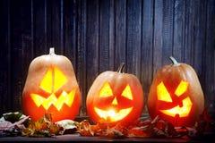 Laternen Jacks O Halloween-Kürbisgesicht auf hölzernem Hintergrund Stockfotos