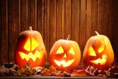 Laternen Jacks O Halloween-Kürbisgesicht auf hölzernem Hintergrund und Lizenzfreie Stockfotos