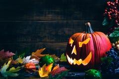 Laternen Jacks O Halloween-Kürbisgesicht auf hölzernem Hintergrund und Herbst treibt Blätter Lizenzfreies Stockfoto