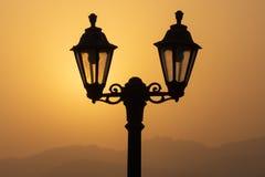 Laternen-Schattenbild bei Sonnenaufgang mit Bergen lizenzfreie stockfotos