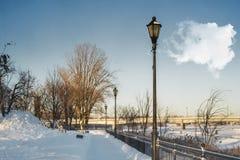 Laternenpfahl auf Promenade neben einem Fluss Lizenzfreie Stockfotografie