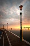 Laternenpfahl durch Wasser bei Sonnenuntergang Lizenzfreies Stockbild
