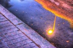 Laternenpfahl refelcted in einer Pfütze bei Sonnenuntergang Stockbild