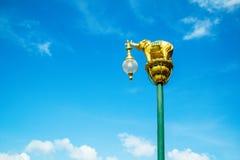 Laternenpfahl verziert mit kleiner goldener Elefantskulptur im Blau stockfotografie