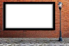 Laternenpfahlstraße, leere Anschlagtafel auf Backsteinmauer Stockfotografie