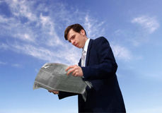 Latest news. Young businessman stands in front of blue sky and reads newspaper Royalty Free Stock Photography