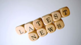 Latest news spelled out in dice falling on white surface Stock Images