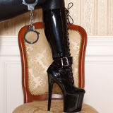 Latex platform boots. Woman in latex boots step up to chair at vintage wall royalty free stock photography