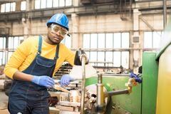 Lathe Operator Posing for Photography. Portrait shot of handsome young lathe operator wearing protective helmet and safety goggles standing at spacious stock photo