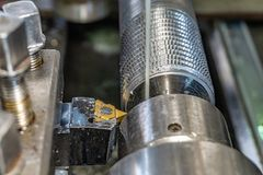Lathe tool cuts machine threads in a factory.  royalty free stock image