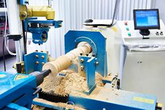 Lathe wood with computer and baluster. In factory stock photo
