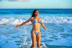 Latijns bikinimeisje die in Caraïbisch strand springen stock afbeeldingen