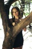 Latijns jong meisje die zich achter een boom bevinden royalty-vrije stock foto