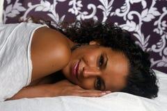 Latijns meisje dat op bedsheets glimlacht Royalty-vrije Stock Afbeelding