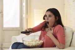 Latijnse de banklaag van de vrouwenzitting thuis in woonkamer het letten op film van de televisie de enge verschrikking stock afbeelding
