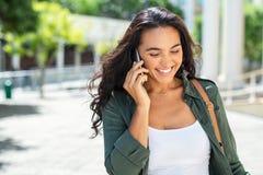 Latijnse glimlachende vrouw die op telefoon spreken royalty-vrije stock foto's