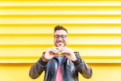 Latijnse Mens die een Hamburger in openlucht eten stock afbeelding