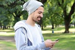 Latijnse mens die zijn smartphone gebruiken outdoors royalty-vrije stock fotografie