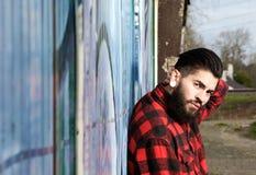 Latijnse mens met baard en doordringen die in openlucht zitten royalty-vrije stock afbeeldingen