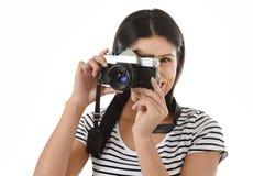 Latijnse vrouw die beelden nemen die door de beeldzoeker van een oude koele retro uitstekende fotocamera kijken Royalty-vrije Stock Afbeelding