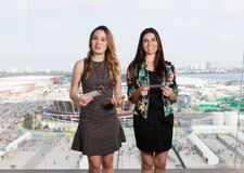 Latijnse vrouwelijke presentator en Kaukasische vrouw die televisie bekijken stock foto's