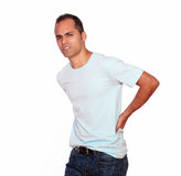 Latin adult man with back pain. Portrait of a latin adult man with back pain looking at you on isolated background Royalty Free Stock Photography