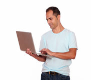 Latin adult man using his laptop computer Stock Images