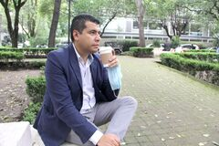 Free Latin Adult Man With Protection Mask, Drinking Coffee In Park, New Normal Covid-19 Royalty Free Stock Image - 195307596