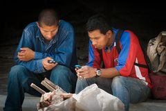 Latin America workers messaging. Two men from Mindo, Ecuador messaging with their mobile phones Stock Images