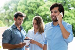 Latin american businessman at phone with other businesspeople. Latin american businessman at phone outdoors with other smart businesspeople stock image