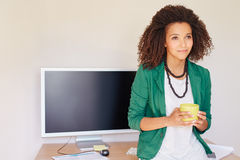 Latin American businesswoman looking thoughtful with a cup of co Stock Photography