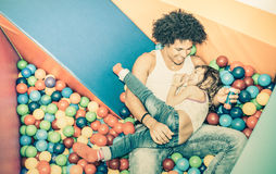 Latin american dad playing with mixed race daughter on ball pit Royalty Free Stock Photo