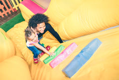 Latin american dad playing with mixed race daughter at playroom. Latin american dad playing with mixed race daughter on inflatable slide at kindergarten playroom stock photo