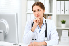 Latin american doctor woman standing with arms crossed and smiling at hospital. Physician ready to examine patient Royalty Free Stock Photo