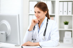 Latin american doctor woman standing with arms crossed and smiling at hospital. Physician ready to examine patient Stock Images