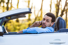 Latin american driver making a phone call while driving Royalty Free Stock Photo