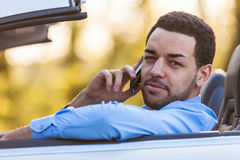 Latin american driver making a phone call while driving Royalty Free Stock Image