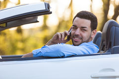 Latin american driver making a phone call while driving Royalty Free Stock Images