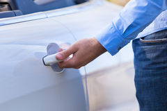 Latin american driver opening his new car door stock images