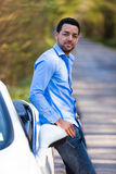 Latin american driver seated on the side of his new car Royalty Free Stock Images